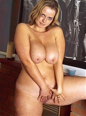 Horny mature babe loosens her top to expose her huge plump breasts and rub her sultry shaved cunt